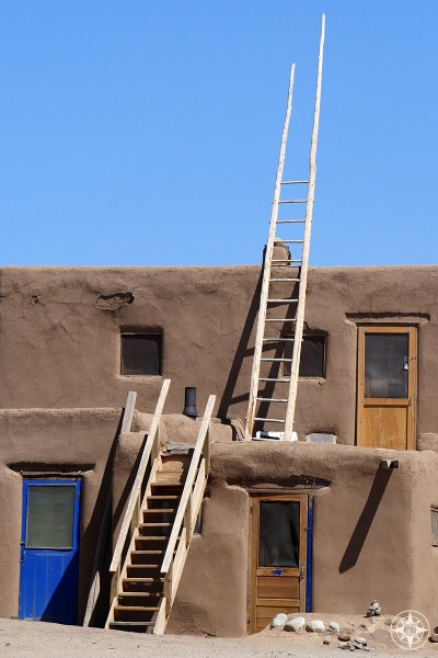 Doors, stairs and ladder reaching into the blue sky at UNESCO World Heritage Site Taos Pueblo, New Mexico.