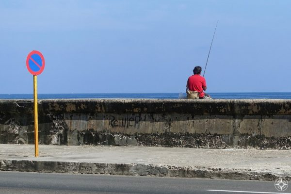 Red and blue traffic sign, man fishing and the sky - Maleón wall, Havana