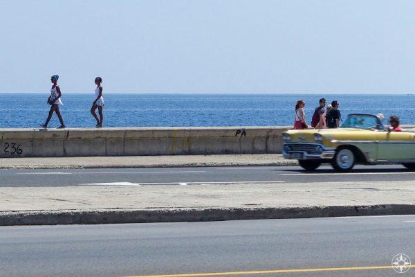 girls walking on seawall, people walking on sidewalk, classic car convertible, blue sea