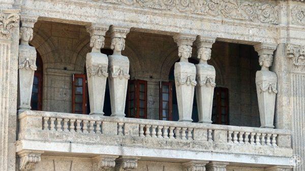 Ornate people pillars on a balcony overlooking the sea along the Malecon, Havana, Cuba