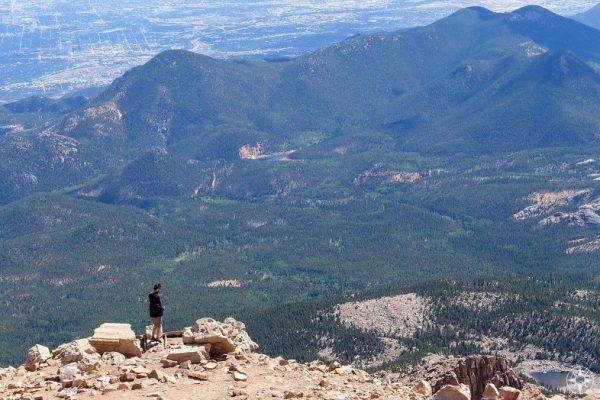 Man walking along summit of Pikes Peak mountain with valley below