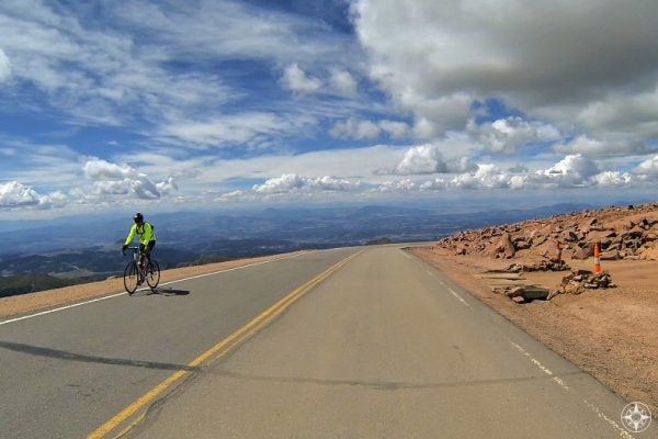 Cyclist riding up Pikes Peak Mountain Road