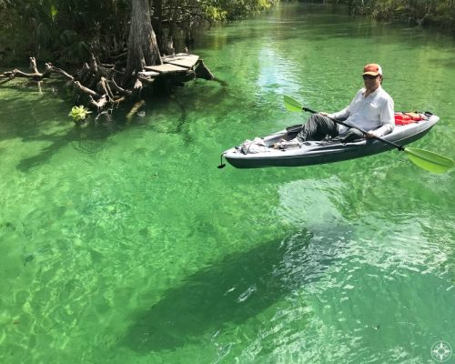 Kayak floating above its shadow on white sand in the clear water of Weeki Wachee River