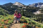Outdoor adventure mystery novel author M.K. Dymock, creator of the Lost Gorge Mysteries, hiking on a mountain trail among wildflowers, Melissa, weekend woman warrior, Happier Place