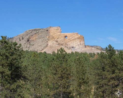 Rising from the woods of the Black Hills, giant Crazy Horse Indian warrior and leader mountain monument.