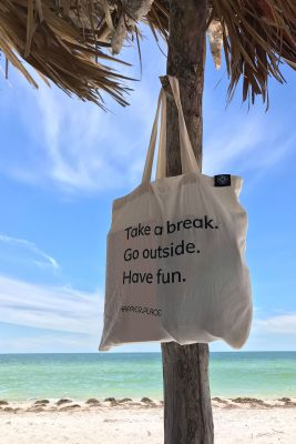 Take a break, go outside, have fun, Happier Place cotton shoulder bag hanging from beach shack, on the beach where Clearwater Beach changes to Caladesi